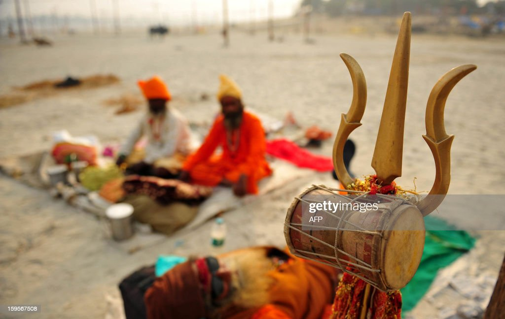 Indian sadhus - holy men - rest on the banks of the Sangam during the Kumbh Mela Festival in Allahabad on January 16, 2013. The Kumbh Mela in the Indian town of Allahabad will see up to 100 million worshippers gather over the next 55 days to take a ritual bath in the holy waters, believed to cleanse sins and bestow blessings. AFP PHOTO/ Sanjay KANOJIA