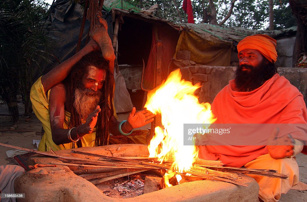 """Indian Sadhus keep warm by a fire and do yoga at their camp on the bank of """"Sangam,"""" the confluence of the three rivers Ganges, Yamuna and mythical Saraswati in Allahabad on December 22, 2012, ahead of the Mahakumbh Mela. The Kumbh Mela, which is scheduled to take place in the northern Indian city in January and February 2013, is the world's largest gathering of people for a religious purpose and millions of people gather for this auspicious occasion. AFP PHOTO/ Sanjay KANOJIA"""