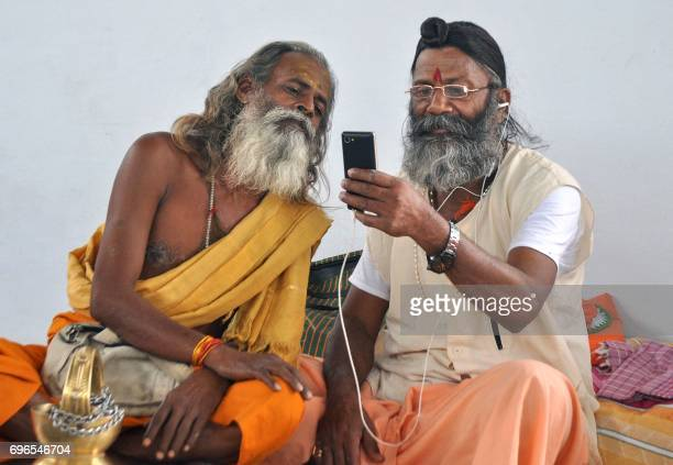 Indian sadhus look at a mobile phone as they await to registr for a pilgrimage at a temple in Jammu on June 16 2017 Sadhus from across India are...