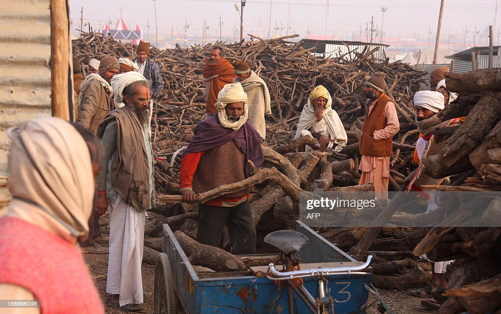 Indian sadhus purchase wood from a government stall at the Kumbh Mela area in Allahabad on January 5, 2013. The Kumbh Mela, which is scheduled to take place in the northern Indian city in January and February 2013, is the world's largest gathering of people for a religious purpose and millions of people gather for this auspicious occasion. AFP PHOTO/ Sanjay KANOJIA
