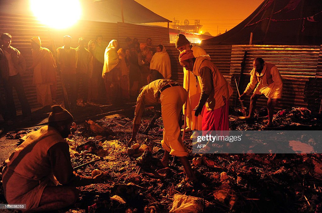 Indian Sadhus (holy men) search for salvageable belongings after a fire destroyed their tents at the Kumbh Mela in Allahabad on January 25, 2013. Nineteen people were injured when a fire broke out at the Triveni area of Kumbh Mela in Allahabad district, a local report said citing officials. The Kumbh Mela in the Indian town of Allahabad will see up to 100 million worshippers gather over the next 55 days to take a ritual bath in the holy waters, believed to cleanse sins and bestow blessings
