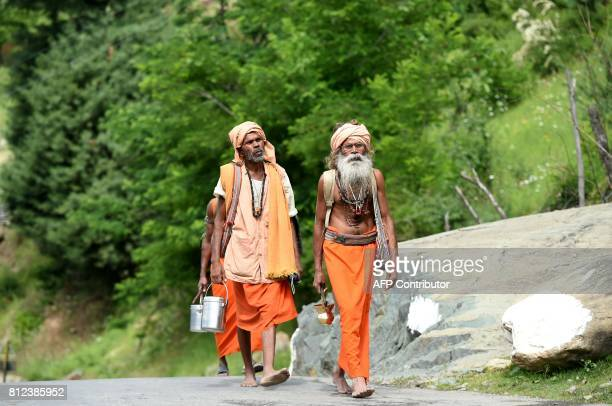 Indian sadhus walk on the road at Chandanwari in Anantnag district some 115 km southeast of Srinagar during the annual Hindu pilgrimage to the...