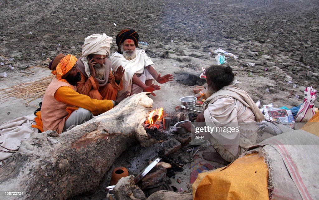"Indian Sadhus warm themselves by a fire on the banks of the ""Sangam,"" the confluence of the three rivers Ganges, Yamuna and mythical Saraswati in Allahabad on December 26, 2012, ahead of The Maha Kumbh Mela. The Kumbh Mela, which is scheduled to take place in the northern Indian city in January and February 2013, is the world's largest gathering of people for a religious purpose and millions of people gather for this auspicious occasion. AFP PHOTO/ Sanjay KANOJIA"