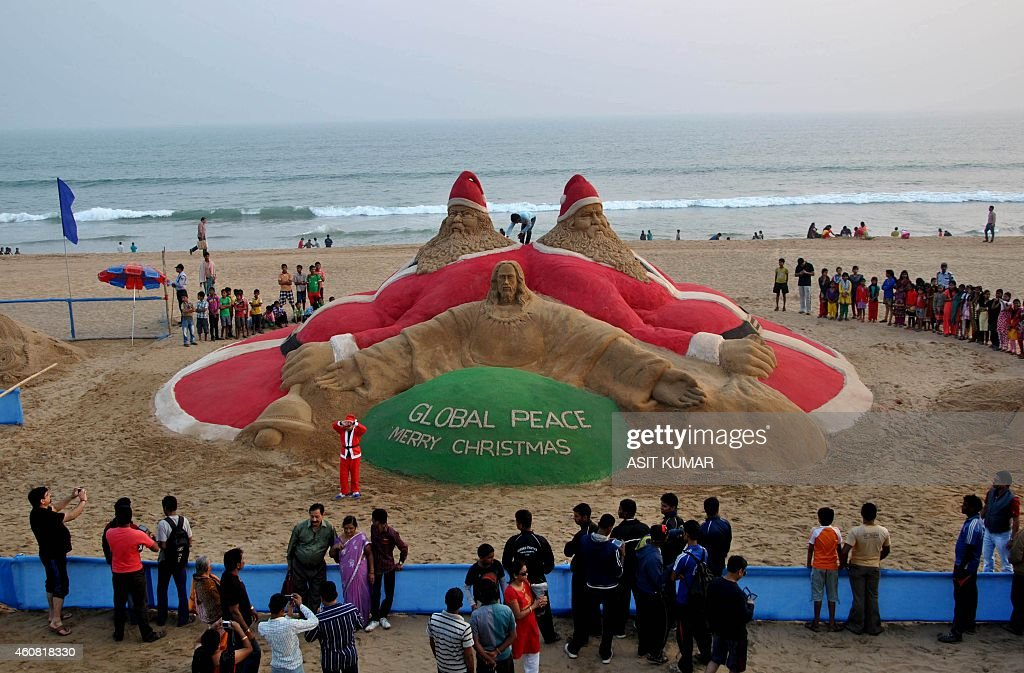 Indian sand artist Sudarsan Pattnaik (C) give the final touches to his sand sculpture depicting Jesus Christ and Santa Claus on Golden Sea Beach at Puri, some 65kms from Bhubaneswar on December 24, 2014. Despite Christians forming a little over 2 percent of the billion plus population in India, with Hindus comprising the majority, Christmas is celebrated with much fanfare and zeal throughout the country. AFP PHOTO/ASIT KUMAR
