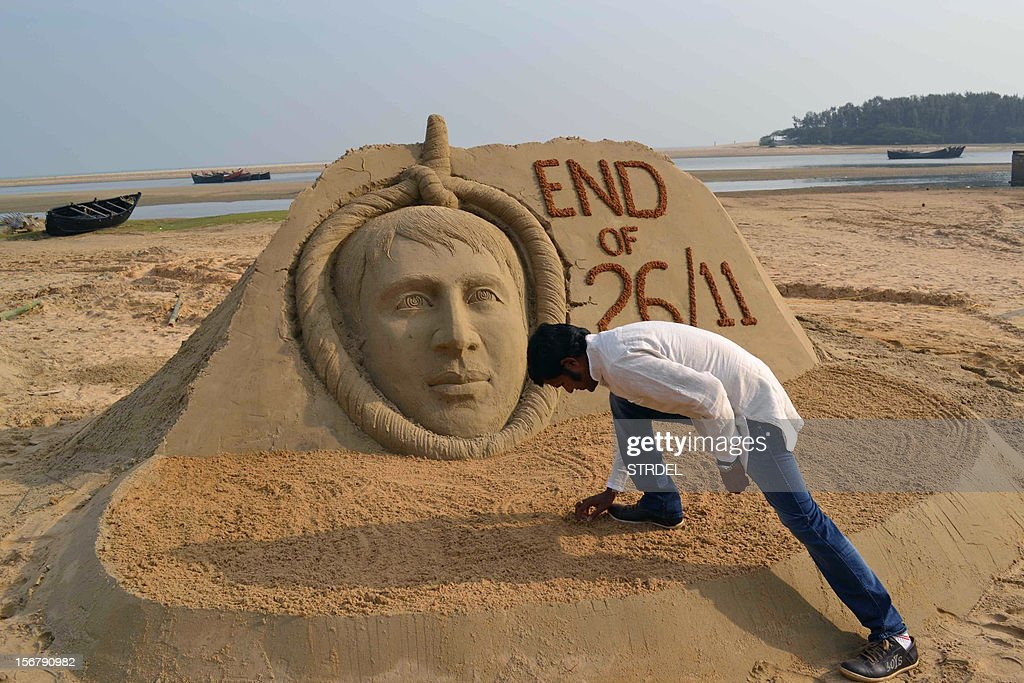 Indian sand artist Sudarsan Pattnaik gives final a touch up on his sand sculpture of Pakistanborn Mohammed Kasab who was the sole surviving gunman of...