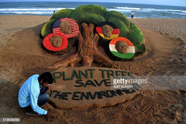Indian sand artist Sudarsan Pattnaik gives the final touches to his sand sculpture featuring four top world leaders Chinese President US President...