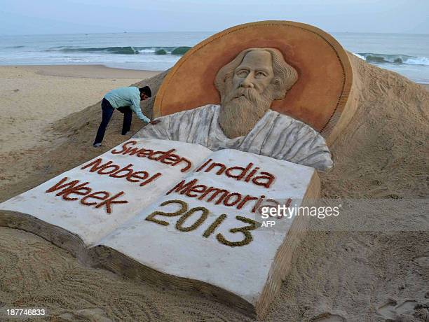Indian sand artist Sudersan Pattnaik gives the final touches to his sculpture of Indian poet Rabindranath Tagore at Golden Sea Beach at Puri some...