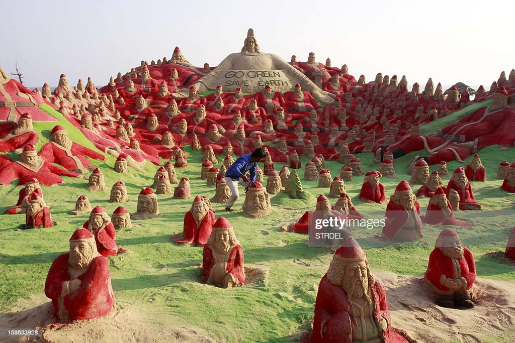 Indian Sand artist Sudersan Pattnaik works on a sand sculpture with over 500 Santa Claus statues at Golden Beach in Puri on about 65 kilometres away from Bhubaneswar on December 22, 2012. Christmas is celebrated on December 25 all over world.