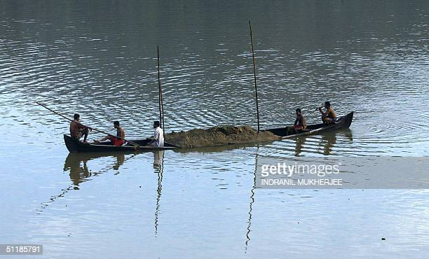 Indian sand miners carry sand in their boat dredged from the bed of the River Chaliyar at Azhinjilam 17 August 2004 Inspite of a state government ban...