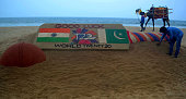 Indian sandartist Sudarsan Pattnaik gives the final touches to a sand sculpture at Puri beach some 65kms south of Bhubaneswar on 18 March 2016 ahead...