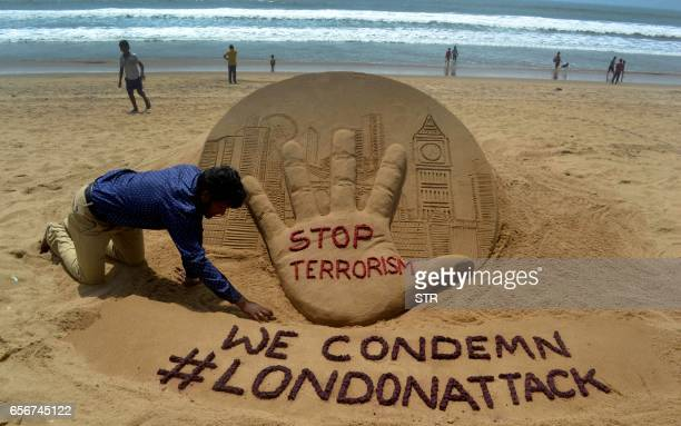Indian sandartist Sudarsan Pattnaik gives the final touches to a sand sculpture on Puri Beach some 65kms from Bhubaneswar on March 23 the day after...