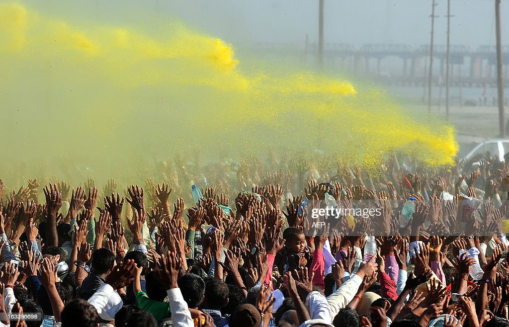 Indian Sant Asaram Bapu (unseen) plays Holi with his followers during the Kumbh Mela festival in Allahabad on March 9, 2013. A record number of 120 million pilgrims have cleansed off their sins after taking a dip in an Indian river during the two-month-long Kumbh Mela festival that draws to an end on March 10. AFP PHOTO/ SANJAY KANOJIA