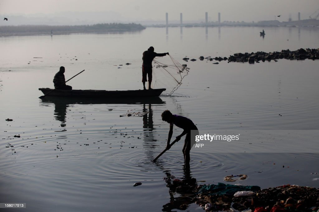 Indian scavengers look for recyclable items near a Hindu bathing site in the polluted Yamuna river in New Delhi on December 9, 2012. India's Supreme Court said on December 8, all parameters of water quality of river Yamuna indicate that it resembles a drain and urged authorities to make it pollution-free. Over 2,400 million liters of untreated sewage flows into the Yamuna every day. AFP PHOTO/ Andrew Caballero-Reynolds