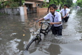 Indian school boys wade along a flooded street following heavy rains in Ahmedabad on July 24 2014 The Indian Metrological Department has predicted...