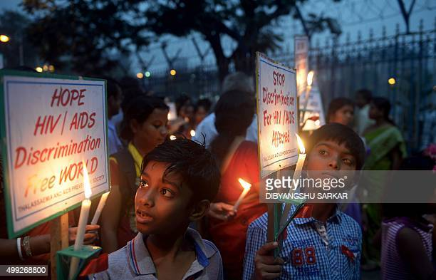 Indian school children and social activists hold candles and posters during a rally to create AIDS awareness on the eve of Worlds AIDS day in Kolkata...
