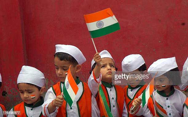 Indian school children dressed in tricolors wave their national flags on the eve of Independence Day celebrations at a school in the northern hill...
