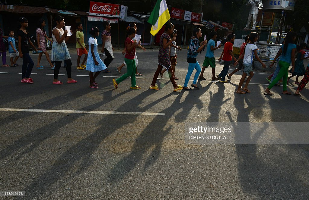 Indian school children hold placards and party flags as they take part in a rally for the support of Gorkhanland during a day long relaxation of an indefinite strike at Sukna village on the outskirts of Siliguri on August 31, 2013. Gorkha People's Liberation Front (GJM) called an indefinite strike throughout the month in Darjeeling and nearby hills. AFP PHOTO/ Diptendu DUTTA