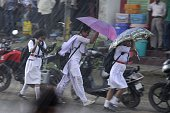 Indian school children shield themselves with an umbrella during a heavy downpour in Agartala capital of northeastern state of Tripura on July 23...