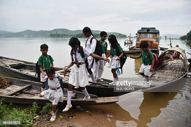 Indian school children step off a boat after crossing flood waters in Rajbari village on the outskirts of Guwahati in Assam state on August 22 2015...