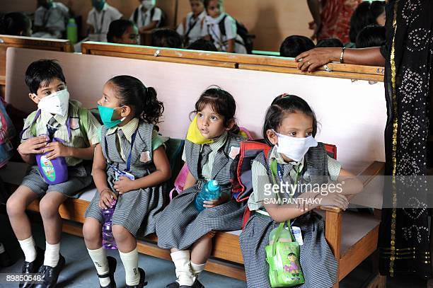 Indian school children wear face masks at school where doctors are performing examinations in Ahmedabad on August 18 2009 as the death toll due to...