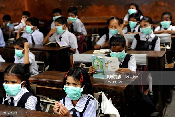 Indian school children wearing protective masks distributed by the local right wing Shiv Sena party for an awareness campaign are seen in a classroom...