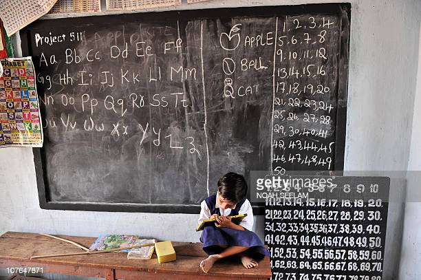 Indian school girl writes on a slate as she attends a government primary school in Hyderabad on June 23 2010 India will introduce China's official...