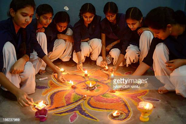 Indian school girls lighting candles as they sit near a 'Rangoli' which is made out of coloured powder during pre Diwali celebration at a school in...