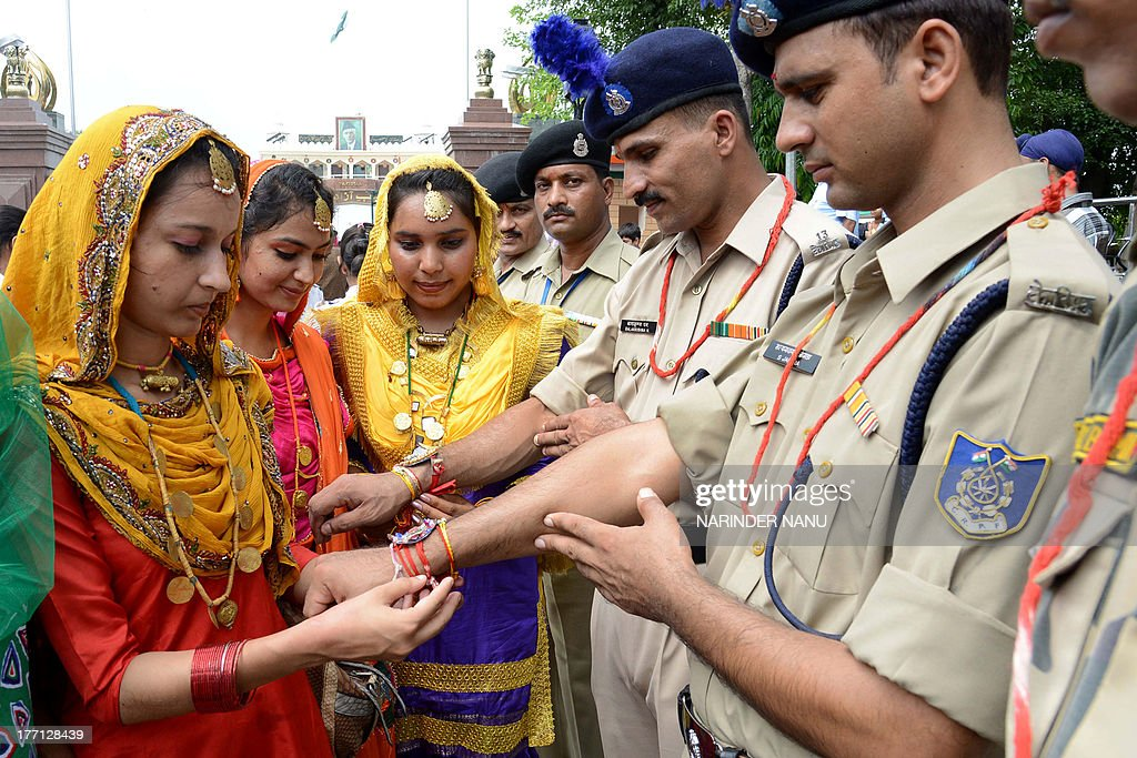 Indian school girls tie a sacred thread or rakhi onto the wrists of Indian Central Reserve Police Force (CRPF) personnel during the Raksha Bandhan festival at the India-Pakistan Wagah Border post on August 21, 2013. The ceremony topically involves a bracelet being tied by a sister to her brother's wrist, symbolising the sister's love and prayers for her brother's well-being, and the brother's vow to protect her. AFP PHOTO/NARINDER NANU