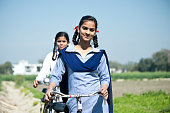 Portrait of Indian school girls in uniform walking with bicycle on field