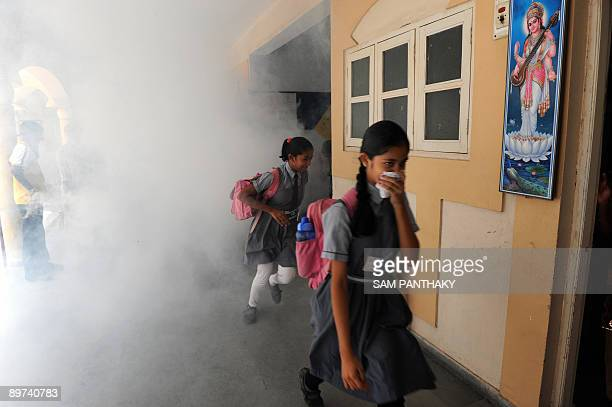 Indian school students run for cover as health workers from Ahmedabad Municipal Corporation fumigate K R Raval Primary school in Ahmedabad on August...