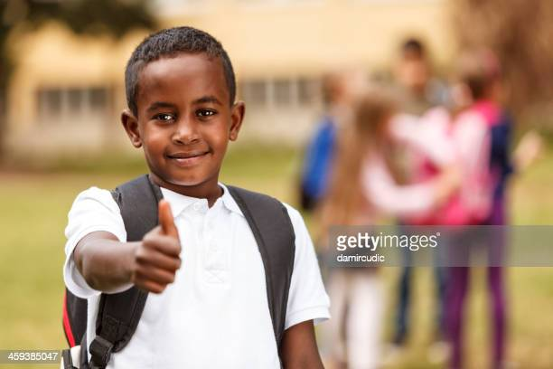 Indian schoolboy giving the thumbs up in front of a group
