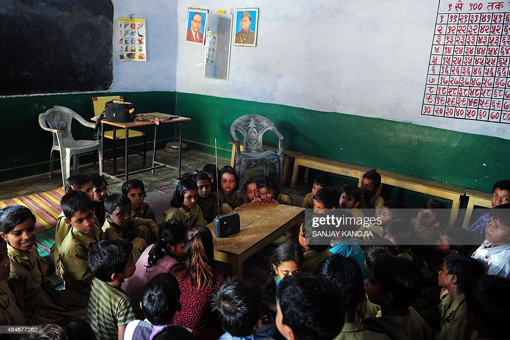 Indian schoolchildren crowd around a radio as they listen to a broadcast by Indian Prime Minister Narendra Modi delivering his Teachers' Day speech...