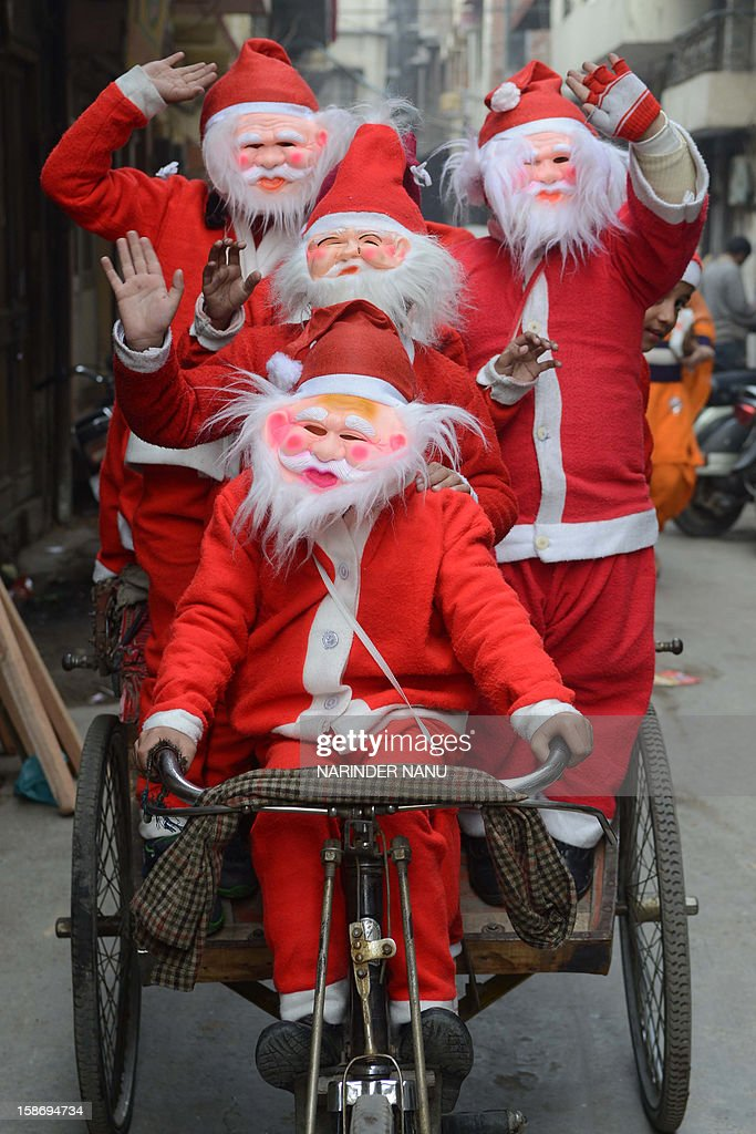 Indian schoolchildren dressed as Santa Claus ride on a cyclerickshaw through a street in Amritsar on December 24 ahead of Christmas Day Despite...