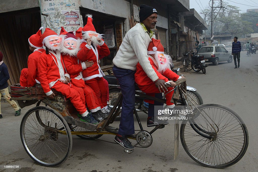 Indian schoolchildren dressed as Santa Claus ride on a cycle-rickshaw through a street in Amritsar on December 24,2012, ahead of Christmas Day. Despite Christians forming a little over 2 percent of the billion plus population in India, with Hindus comprising the majority, Christmas is celebrated with much fanfare and zeal throughout the country.