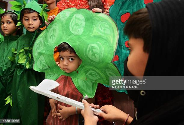 Indian schoolchildren dressed as trees take part in an event to highlight environmental issues on the eve of World Environment Day in Amritsar on...