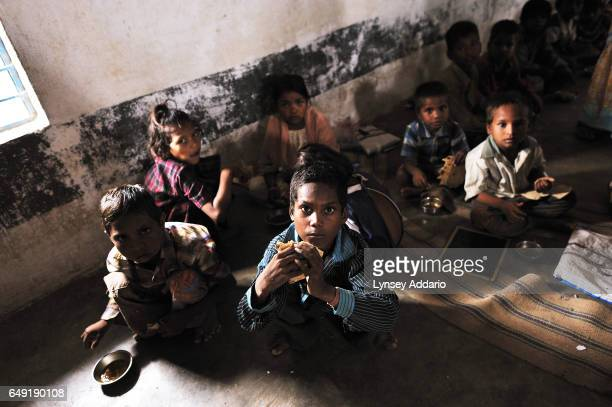 Indian schoolchildren eat lunch together as part of the nationwide 'Midday Meal' program in Jhabua Madhya Pradesh India on July 16 2010 Due to the...