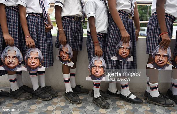 TOPSHOT Indian schoolchildren hold masks bearing the image of former Indian president APJ Kalam ahead of the first anniversary of his death during a...