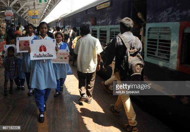 Indian schoolchildren hold placards as they take part in a tuberculosis awareness campaign at a railway station in Chennai on March 24 on World...