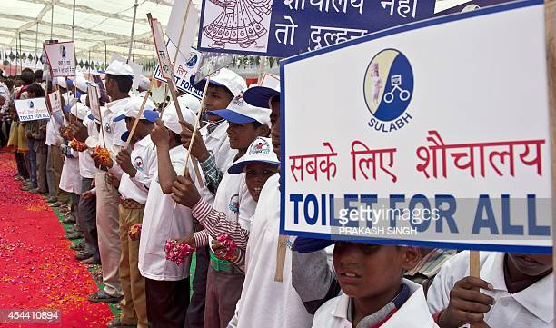 Indian schoolchildren hold placards as they welcome Bindeshwari Pathak founder and chairman of NGO Sulabh International at Katra Sahadatgunj village...