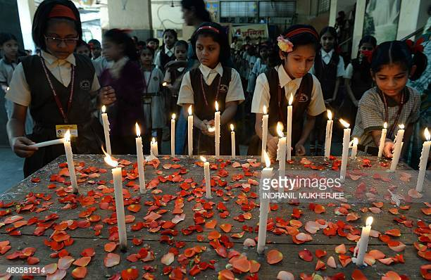 Indian schoolchildren light candles at their school in Mumbai on December 17 in memory of schoolchildren killed during an attack on an army school in...