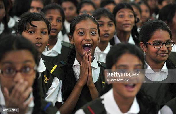 Indian schoolchildren react after watching a tiger on a giant screen during a 'Kids for Tigers' programme on the eve of World Tiger Day at Hyderabad...