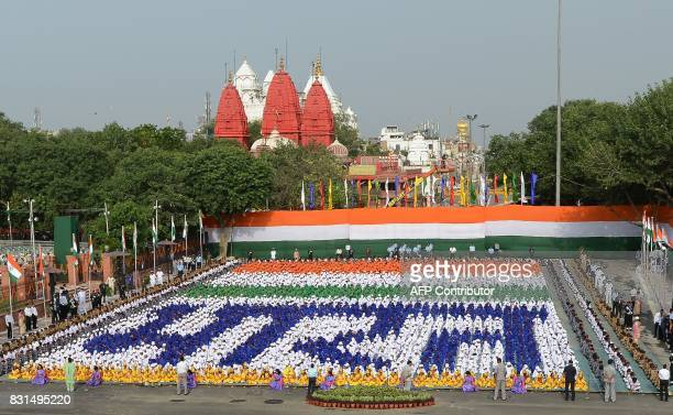 Indian schoolchildren sit in formation forming Hindi script that reads 'Bharat' during the country's 71st Independence Day celebrations which marks...