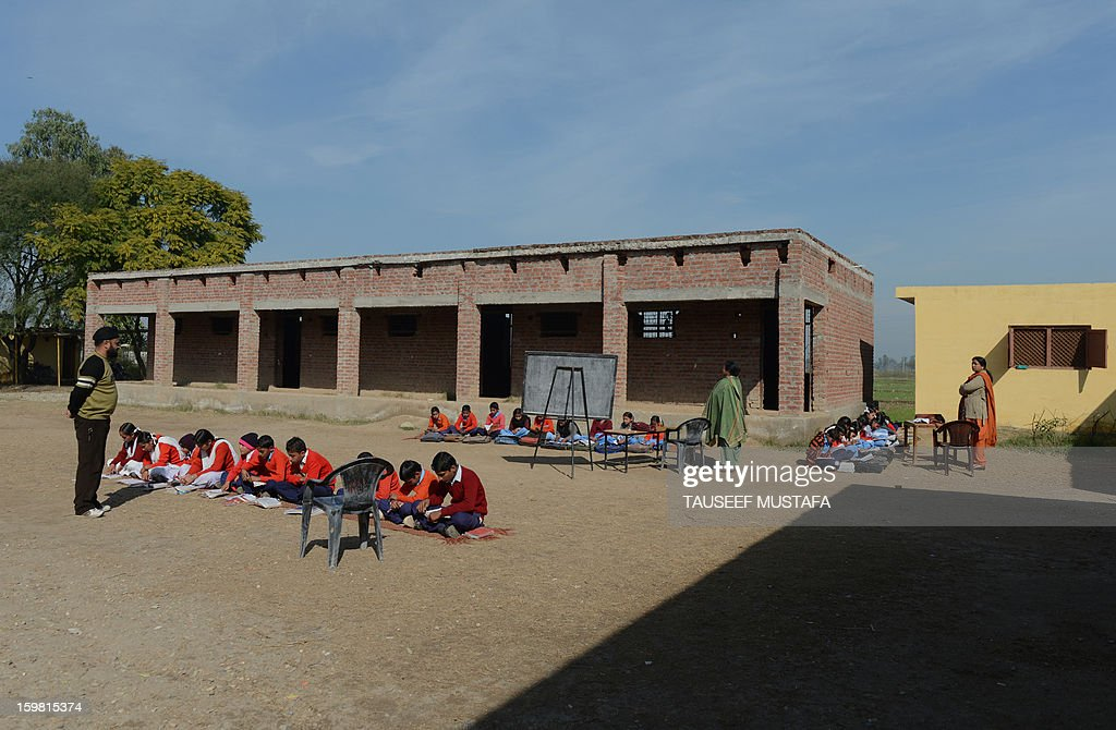 Indian schoolchildren sit inside a school near the India-Pakistan border in Suchit-Garh, some 36 kms southwest of Jammu, on January 21, 2013. On both sides of the de facto border in Kashmir, villagers living on one of the world's most dangerous flash points have special reason to fear the return of tension between India and Pakistan. The spike in cross-border firing in Kashmir -- a region claimed wholly by both India and Pakistan -- has seen five soldiers killed in recent days and threatened to unravel a fragile peace process that had begun to make progress. AFP PHOTO/ Tauseef MUSTAFA