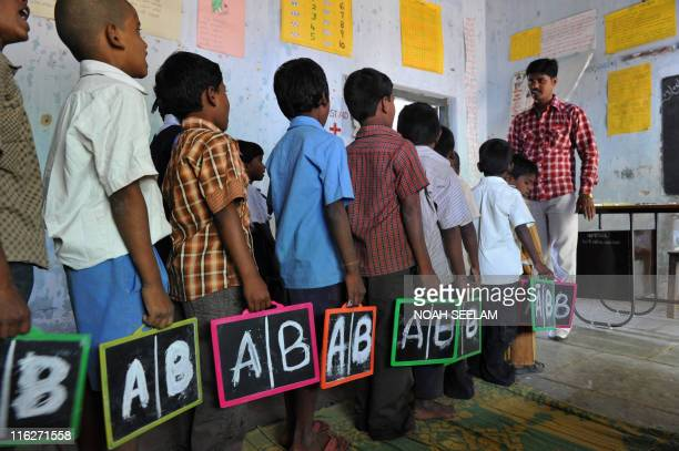 Indian schoolchildren stand in line with English alphabets written on their slates at a government primary school in the outskirts of Hyderabad on...