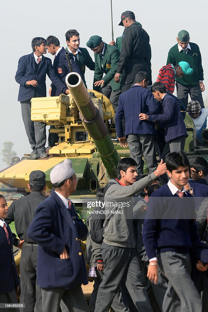 Indian schoolchildren stand on a T-90S/SK tank during an Army Mela (fair) and exhibition at Khasa, some 15 kms from Amritsar, on December 17, 2012. The Army Mela (fair ), organised by the Vajra Corps, displayed weapons, tanks, aircraft and military equipment to students and civilian visitors of the event. AFP PHOTO/ NARINDER NANU