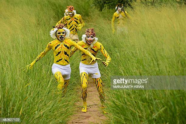 Indian schoolchildren their face and bodies painted as tigers run at a park in Bangalore on August 1 during an awarness programme about the...