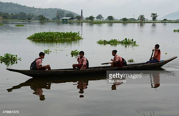 Indian schoolchildren use a boat to navigate floodwater in Rajbari village on the outskirts of Guwahati on June 13 2015 Flooding in India's...