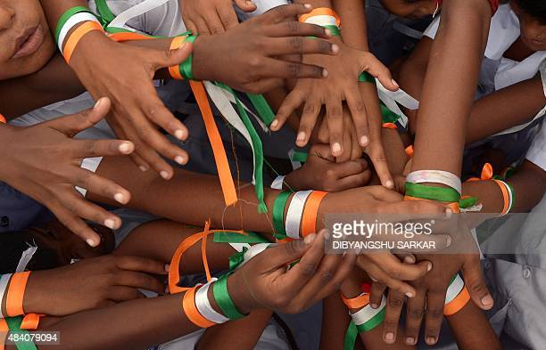 Indian schoolchildren with tricolour bands on their wrists play a game prior to Independence Day celebrations at a school in Kolkata on August 15...