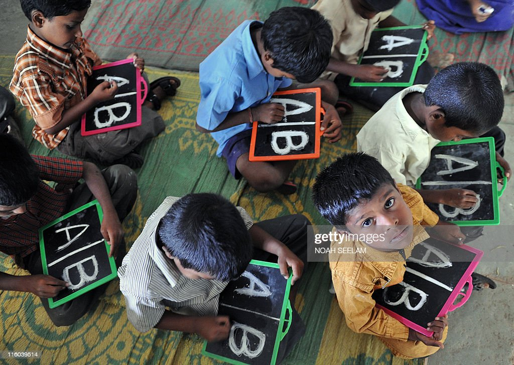 Indian schoolchildren write English alphabets on slates at a government primary school in the outskirts of Hyderabad on June 13, 2011, on the opening day of the new academic year. The government of India's Andhra Pradesh state has introduced English as a second language from Class 1 onwards for the 2011-2012 academic year. India's National Knowledge Commission has admitted that no more than one percent of country's population uses English as a second language. AFP PHOTO/Noah SEELAM