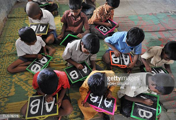 Indian schoolchildren write English alphabets on slates at a government primary school in the outskirts of Hyderabad on June 13 on the opening day of...